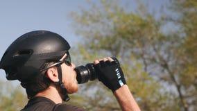 Retrato do verso da ?gua pot?vel do ciclista antes de treinar o equipamento, o capacete e ?culos de sol pretos vestindo vídeos de arquivo