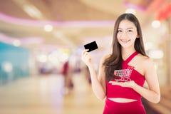 Retrato do vestido vermelho asiático do desgaste de mulher que guarda o carro e o cartão de crédito Fotografia de Stock Royalty Free