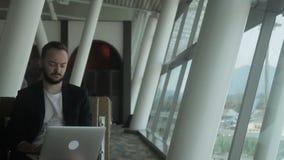 Retrato do viajante masculino novo, que está olhando à tela do portátil no aeroporto vídeos de arquivo