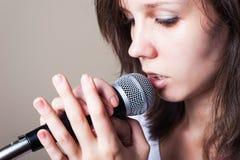Retrato do vocalista fêmea no close up cinzento do fundo fotografia de stock