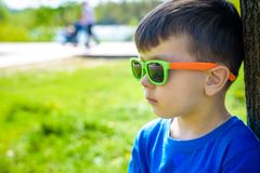 Retrato dos óculos de sol vestindo do rapaz pequeno esperto que smirking fotografia de stock