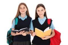 Retrato dos adolescentes na farda da escola com trouxas e livros fotos de stock royalty free
