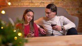 Retrato dos amigos caucasianos novos que sentam-se no assoalho e no vinho bebendo que falam um com o otro no Natal confortável vídeos de arquivo