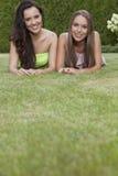 Retrato dos amigos fêmeas novos atrativos que relaxam no parque Imagem de Stock Royalty Free