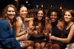 Retrato dos amigos fêmeas que apreciam a noite para fora na barra do telhado foto de stock royalty free