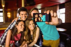 Retrato dos amigos felizes que tomam uma foto com um telefone Fotografia de Stock Royalty Free