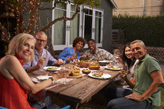 Retrato dos amigos maduros que apreciam a refeição exterior no quintal imagem de stock