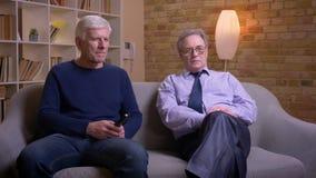 Retrato dos amigos masculinos superiores que sentam-se junto no sof? que olha a tev? e que discute ativamente video estoque