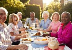 Retrato dos amigos superiores que apreciam o partido de jantar exterior em casa imagens de stock royalty free