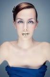 Retrato dos azuis celestes de uma jovem mulher com bordos dourados Imagem de Stock Royalty Free