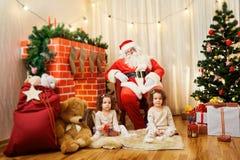 Retrato dos bebês gêmeos de Santa Claus e da menina, criança na sala b imagem de stock
