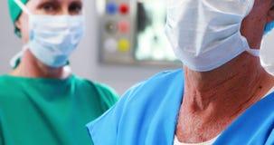 Retrato dos cirurgiões que vestem a máscara cirúrgica no teatro de operação vídeos de arquivo