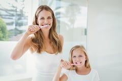 Retrato dos dentes de escovadela felizes da mãe e da filha fotografia de stock royalty free