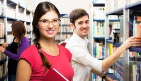 Retrato dos estudantes em uma biblioteca imagens de stock royalty free