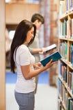 Retrato dos estudantes que lêem ao estar acima Imagens de Stock