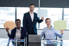 Retrato dos executivos felizes que guardam a bolha do discurso fotografia de stock