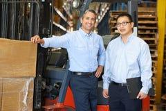 Retrato dos homens de negócios com o caminhão de empilhadeira no armazém Fotografia de Stock Royalty Free
