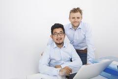 Retrato dos homens de negócios com o portátil na mesa no escritório Foto de Stock Royalty Free