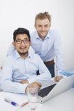 Retrato dos homens de negócios com o portátil na mesa no escritório Fotografia de Stock Royalty Free