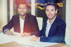 Retrato dos homens de negócios que sentam-se em sua mesa Fotos de Stock Royalty Free