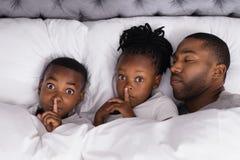 Retrato dos irmãos com o dedo nos bordos pelo pai que dorme na cama fotografia de stock