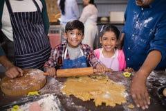 Retrato dos irmãos de sorriso que preparam o alimento com pais na cozinha fotos de stock