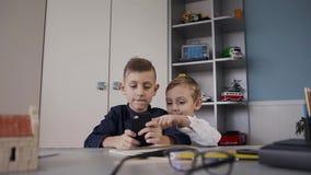 Retrato dos irmãos mais novo que estão usando o smartphone conversando com o amigo que se senta na mesa em casa vídeos de arquivo