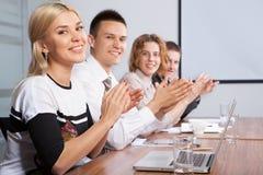 Retrato dos jovens de aplauso bem sucedidos que sentam-se na linha Imagens de Stock