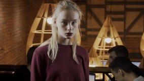 Retrato dos jovens e mulher da forma no café no fundo dos povos filme