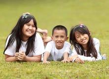 Retrato dos miúdos felizes que encontram-se na grama Imagens de Stock