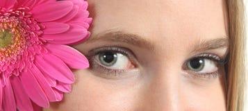 Retrato do olhos azuis bonitos de uma mulher com uma flor cor-de-rosa Imagem de Stock Royalty Free