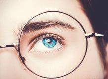 Retrato dos olhos azuis vestindo dos monóculos de um menino perto, tiro macro do estúdio imagens de stock royalty free