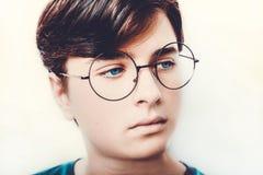 Retrato dos olhos azuis vestindo dos monóculos de um menino perto, tiro macro do estúdio fotos de stock