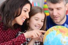 Retrato dos pais e da filha que olham o globo do mundo fotos de stock royalty free