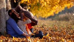 Retrato dos pais e das crianças na folha do outono que passam o tempo junto video estoque
