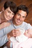 Retrato dos pais que alimentam o bebê recém-nascido em casa Fotografia de Stock Royalty Free