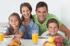 Retrato dos pais que comem o café da manhã com suas crianças imagem de stock