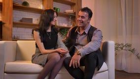 Retrato dos pares árabes que falam agradavelmente um com o otro o assento no sofá na sala de visitas vídeos de arquivo