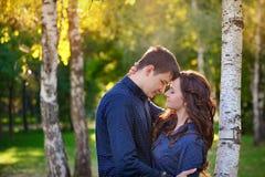 Retrato dos pares adolescentes românticos que sentam-se no parque Fotos de Stock