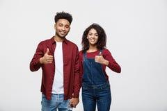 Retrato dos pares afro-americanos atrativos que mostram o polegar acima sobre o fundo branco do estúdio imagens de stock royalty free