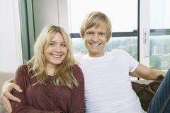 Retrato dos pares alegres que sentam-se no sofá em casa Imagem de Stock