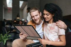 Retrato dos pares bonitos novos que sentam-se no restaurante com menu nas mãos Menina afro-americano agradável com encaracolado e imagem de stock royalty free