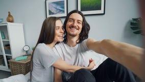 Retrato dos pares bonitos que fazem a chamada video em linha na cama em casa que fala o beijo filme