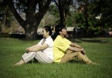 Retrato dos pares bonitos que sentam-se na terra no parque Fotografia de Stock Royalty Free