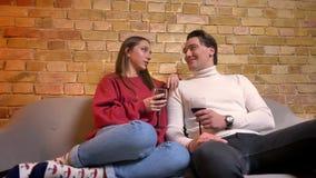 Retrato dos pares caucasianos novos que sentam-se no sofá e no vinho bebendo que comunicam-se um com o otro na casa confortável vídeos de arquivo
