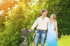 Retrato dos pares caucasianos que têm uma caminhada no parque com bicicleta Fotos de Stock Royalty Free