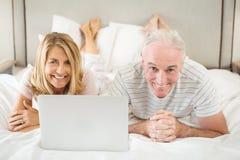 Retrato dos pares de sorriso que encontram-se na cama e que usam o portátil Fotografia de Stock Royalty Free