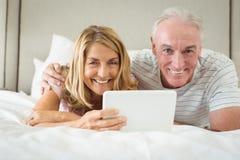 Retrato dos pares de sorriso que encontram-se na cama e que usam o portátil Imagens de Stock Royalty Free
