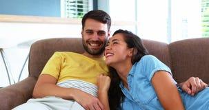 Retrato dos pares de sorriso que relaxam no sofá na sala de visitas vídeos de arquivo