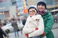 Retrato dos pares felizes que abraçam na rua da cidade durante o inverno Fotografia de Stock Royalty Free
